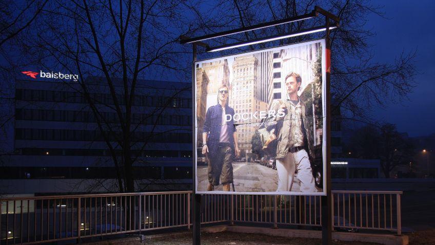 Die  Balkenleuchte  Bright  Stripes  beleuchtet  das  Plakat  eines  Werbeträgers  in  der  Nacht.