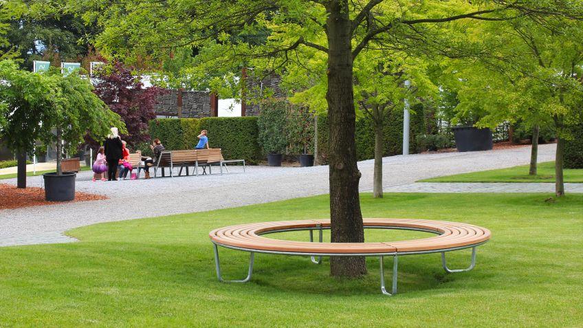 Geschlossene  Landi  Rundbank  in  der  Ausführung  Lärche  um  einen  Baum  in  einer  Parkanlage.