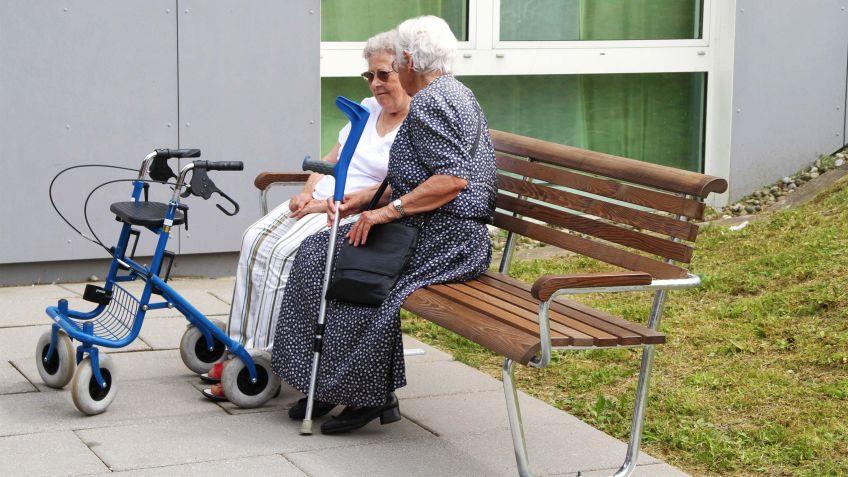Landi  Seniorenbank  mit  Rücken-  und  Armlehne  in  der  Ausführung  NATWOOD  in  einem  Seniorenheim.