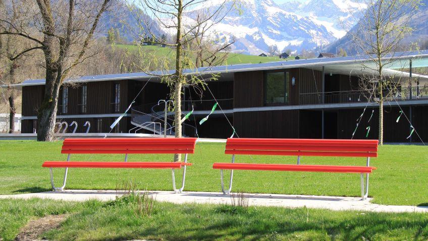 Die Rote Landi Sitzbank Mit Rückenlehne Prägt Das Schweizer Landschaftsbild.