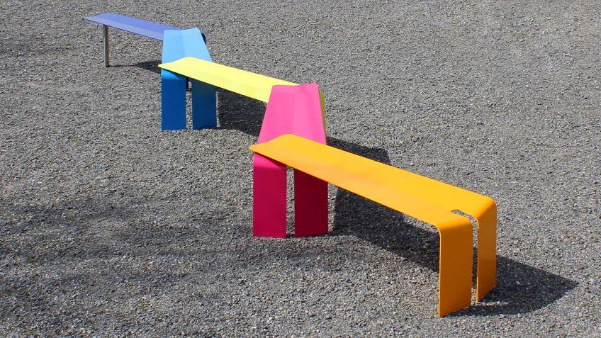 Plico  Bänke  kombiniert  zu  einer  farbenfrohen,  langen  Sitzkonfiguration  auf  einem  Schulhof.