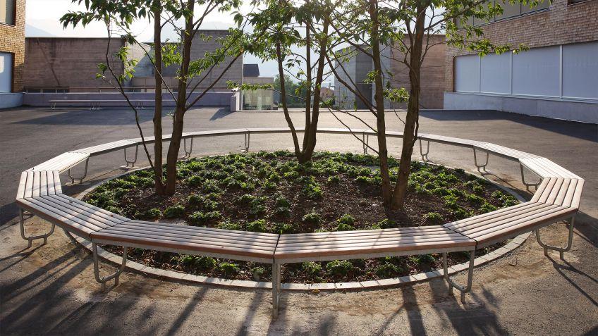 Landi  Mehreckbank  als  geschlossene  Formation  um  eine  Baumgruppe  auf  einem  Schulhof.