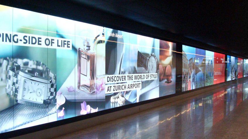 Die  aneinander  gereihten  Gross  Leuchtkästen  prägen  das  Bild  einer  Durchgangshalle  im  Flughafen  Zürich.