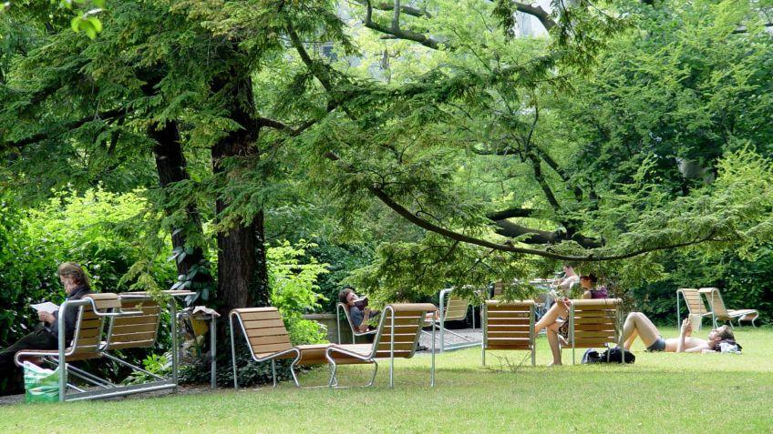 Die  ausgehängten  Portami  Sessel  aus  Lärchenholz  frei  aufgestellt  zu  einer  Sitzgruppe  im  Grünen.
