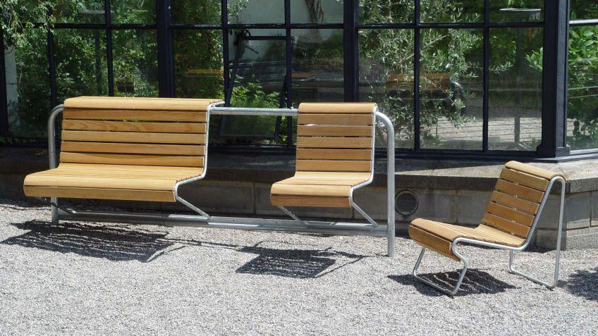Portami  als  Einzelplatzbank  in  der  Ausführung  Lärche  in  einer  Parkanlage.