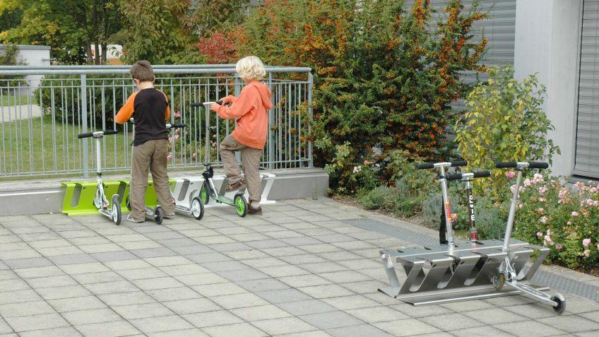 KickboardZ  Twinset  aus  Edelstahl,  frei  aufgestellt  auf  einem  Schulhof  für  beidseitiges  Abstellen  von  Kickboardz.