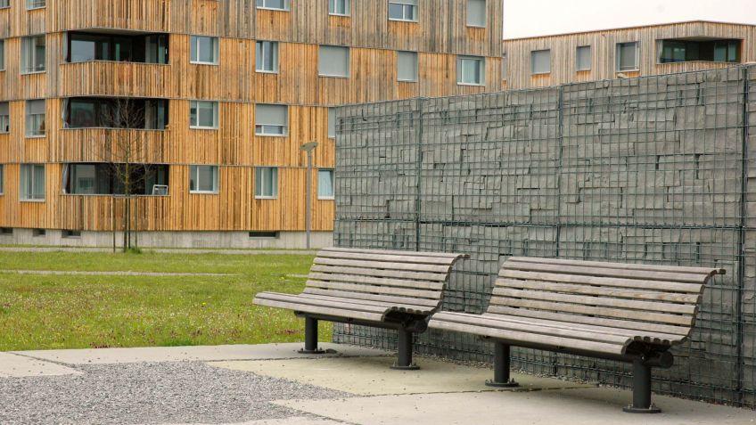 Uni  Sitzbank  mit  Rückenlehne  und  verwitterter  Lärche-Sitzfläche  in  einer  Wohnanlage.