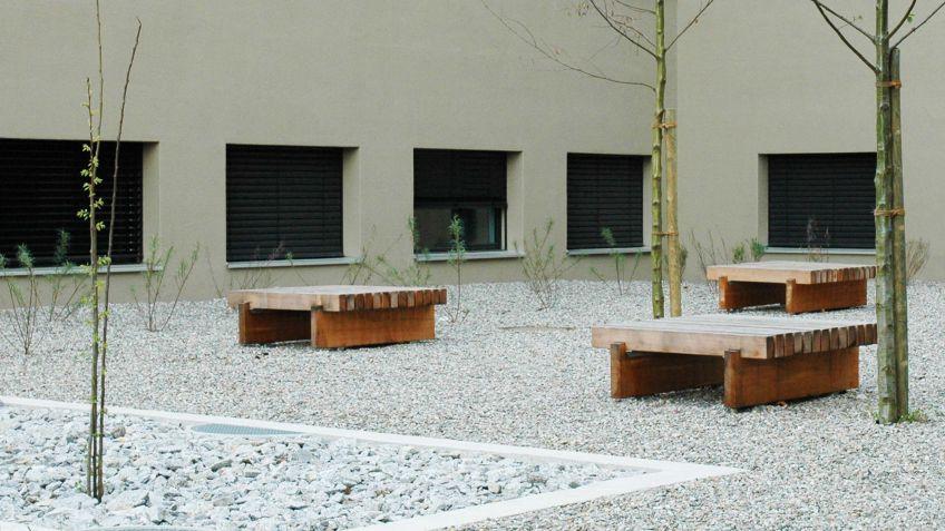 Quadratische  Sol  Sitzinseln  aus  lasiertem  Massivholz  in  einer  Wohnanlage.