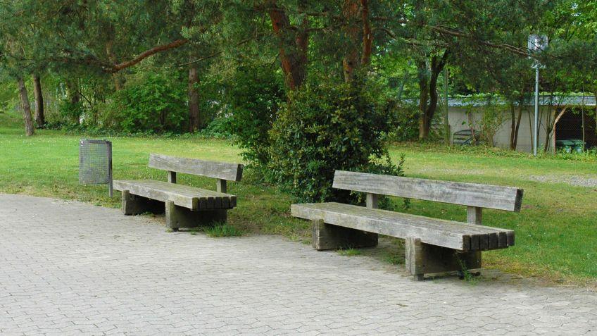 Sol  Sitzbank  mit  Rückenlehne  geprägt  von  den  Zeichen  der  Zeit  in  einer  öffentlichen  Parkanlage.