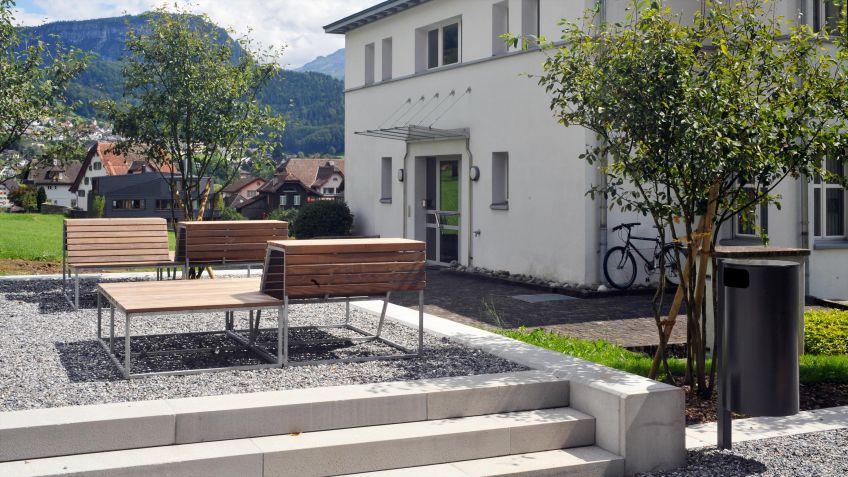 Der  Public  Bin  Abfallkübel  110L  in  einer  Wohnanlage  zusammen  mit  dem  Landscape  Sitzmobiliar.