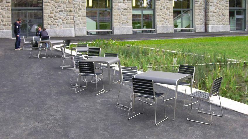 Impetus  Tisch  mit  massiver  Eternit-Platte  zusammen  mit  BURRI02  Stühlen  in  historischem  Kontext.