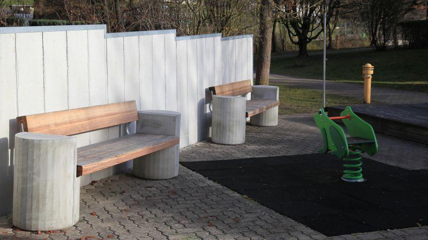Riva  Sitzbank  mit  verwitterten  Holzlatten  in  einer  Wohnanlage.