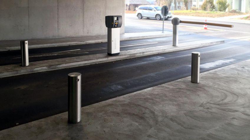 Niederflurpoller  mit  individueller  Höhe  und  Durchmesser  säumen  die  Einfahrt  eines  Parkhauses.