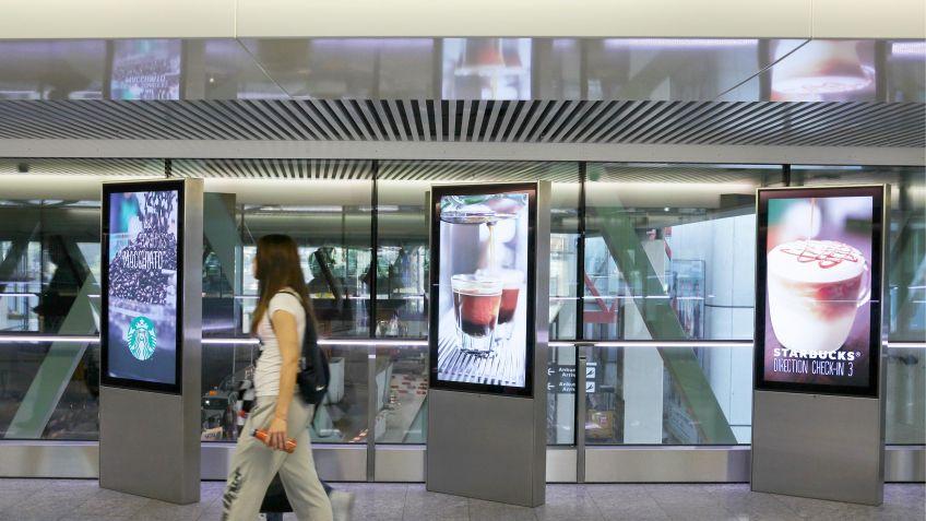 Die  Werbeanzeigen  der  einseitigen  Monitorstele  begleiten  die  Passagiere  auf  dem  Weg  durch  den  Flughafen  Zürich.