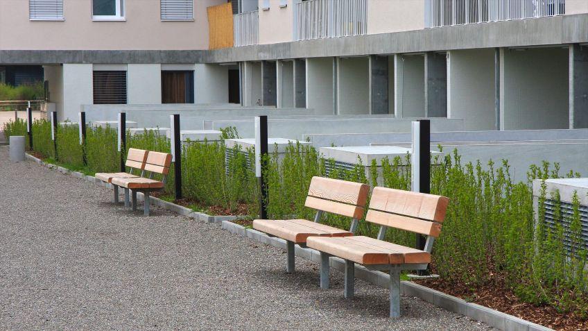 Die  zeitlose  Parkbank  mit  Rückenlehne  in  der  Ausführung  Lärche  lädt  zum  Verweilen  in  einer  Wohnanlage.