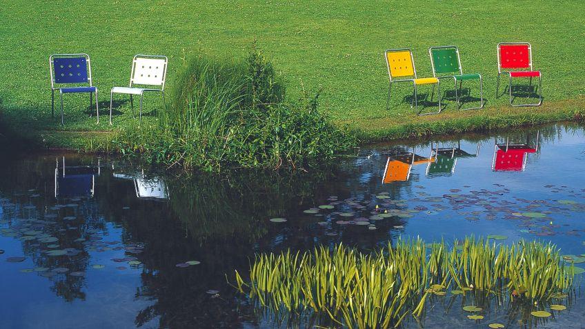 Stella  Stühle  aus  wetterfester  Metallkonstruktion  setzen  farbige  Akzente  im  Grün  der  Natur.