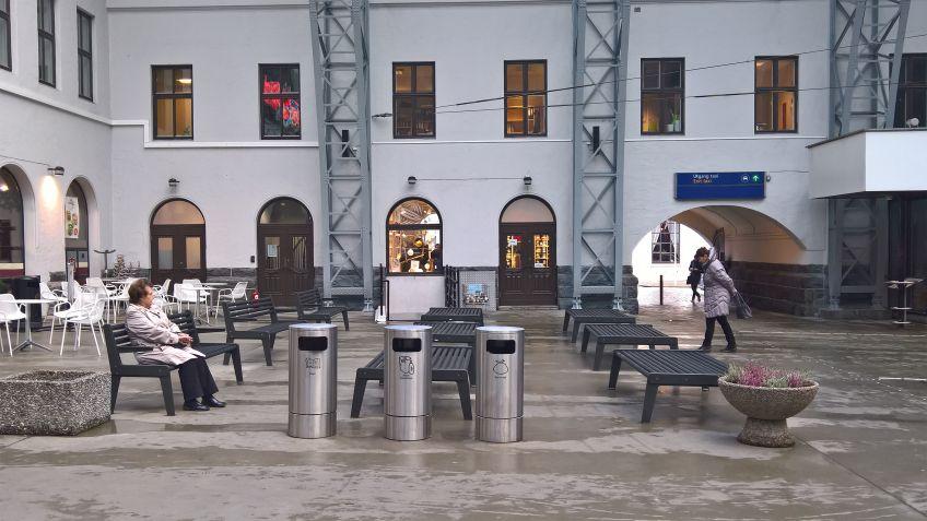 In  der  Halle  stehen  BURRI  02  Sitzbänke  und  drei  spezialangefertigte  sowie  beschriftete  Public  Bin  Entsorgungssysteme.