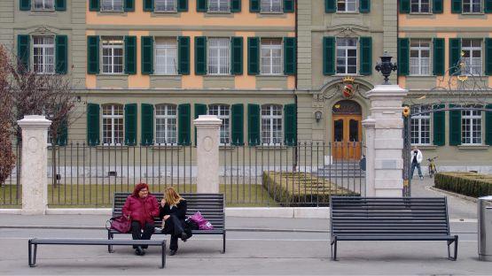 BURRI  02  mit  hoher  Rückenlehne  und  Bank  ohne  Rückenlehne  vor  historischem  Gebäude.